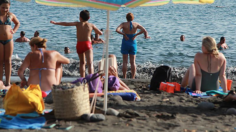 Touristen am Strand von La Calera